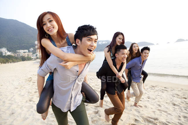 Chinese people playing piggyback on beach in Repulse Bay, Hong Kong — Stock Photo