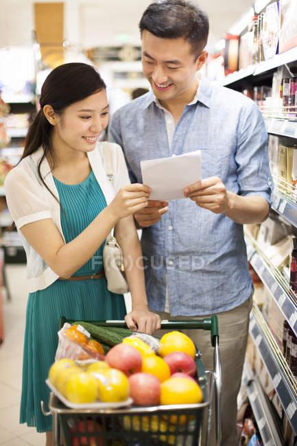 Casal de chineses leitura lista de compras no supermercado — Fotografia de Stock