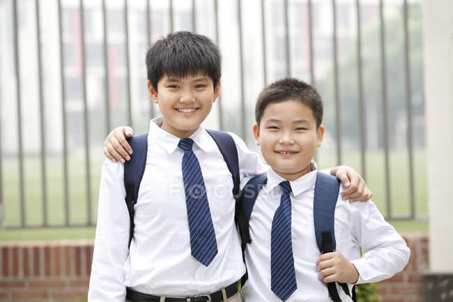 Веселые одноклассники в школьной форме на улице — стоковое фото