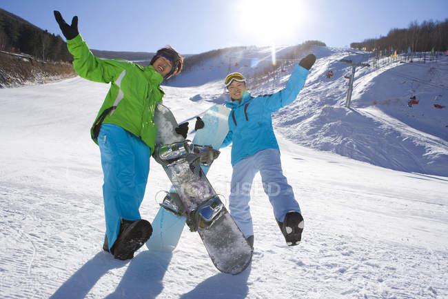 Китайский мужчина и женщина с сноуборды позирует на горнолыжном курорте — стоковое фото