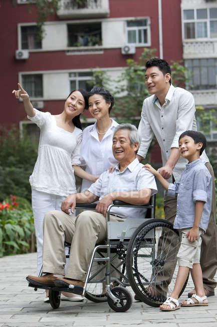 Китайская семья с дедушкой в инвалидной коляске стоит на улице и смотрит на вид — стоковое фото
