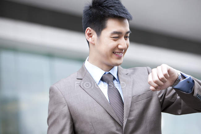 Chinese businessman looking at wristwatch on street — Stock Photo