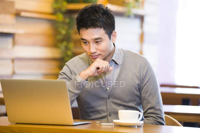 Hombre chino navegando por la red en la cafetería - foto de stock