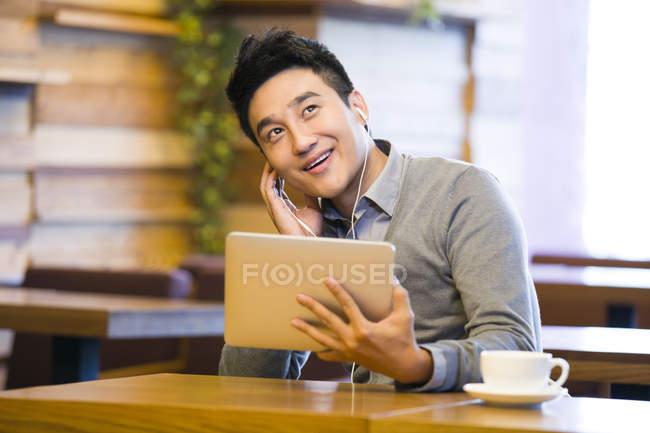 Китайська людина користуються музики в цифровий планшетний в кафе — стокове фото