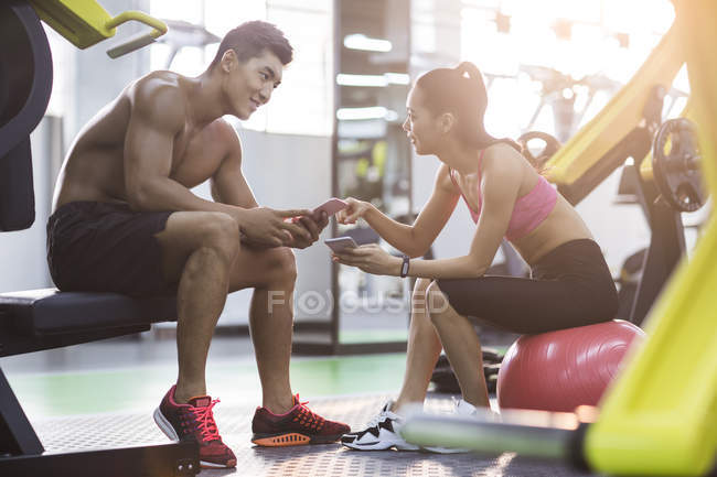 Chinese couple resting at gym and using smartphones — Stock Photo