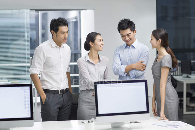 Chinese business people standing at computer monitors in office — Stock Photo