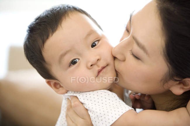 Chinese woman kissing infant son — Stock Photo