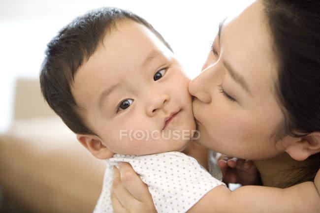 Donna cinese baciare figlio neonato — Foto stock