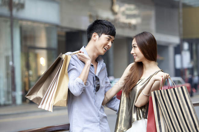 Chinese couple looking at each other while shopping in street — Stock Photo