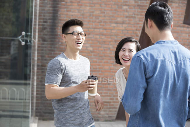 Chinese friends talking and laughing with coffee at street — Stock Photo