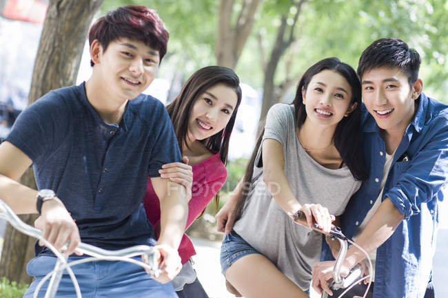 Chinese friends sitting on bicycles on street — Stock Photo