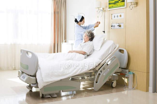 Enfermeira chinês mudando o soro no quarto da paciente — Fotografia de Stock