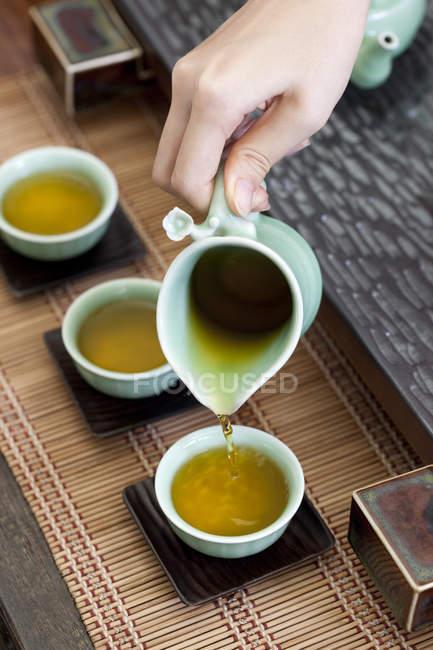 Gros plan de femme main verser le thé dans les tasses à thé — Photo de stock