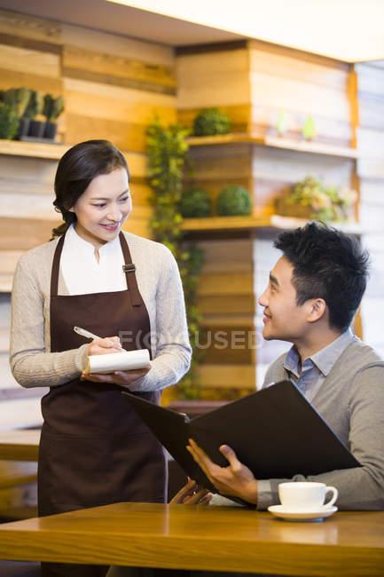 Hombre chino de ordenar a mujer camarera en cafetería - foto de stock
