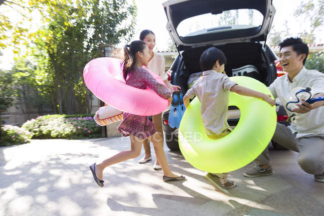 Chinese siblings wearing swimming tubes running to car with parents — Stock Photo
