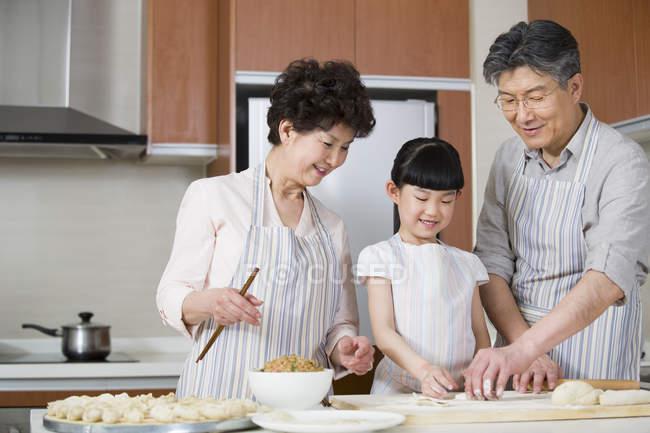 Chinois grands-parents et petite-fille faire des boulettes dans la cuisine — Photo de stock