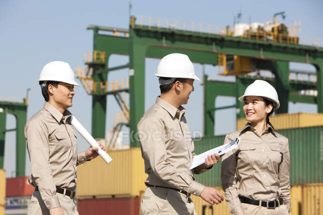 Chinese shipping industry workers talking at dock — Stock Photo