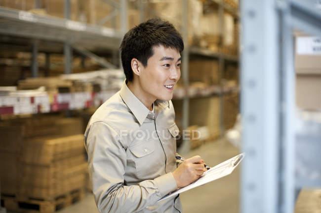 Trabajador almacén chino hombre escribir con portapapeles - foto de stock