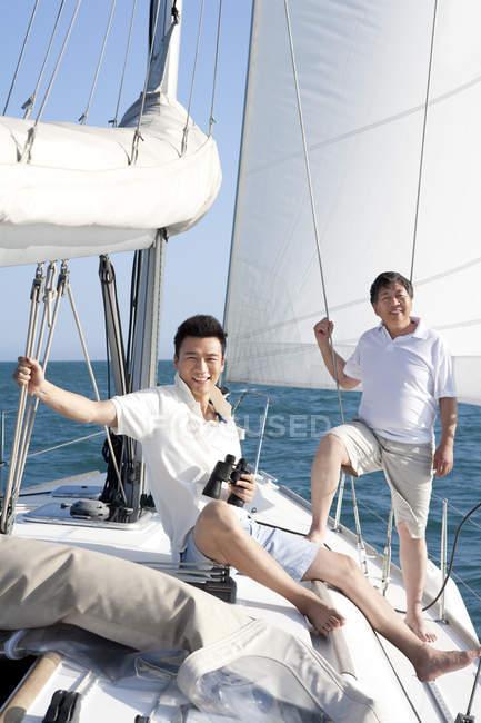 Китайської молоді і старшого чоловіків, плавання на яхті — стокове фото