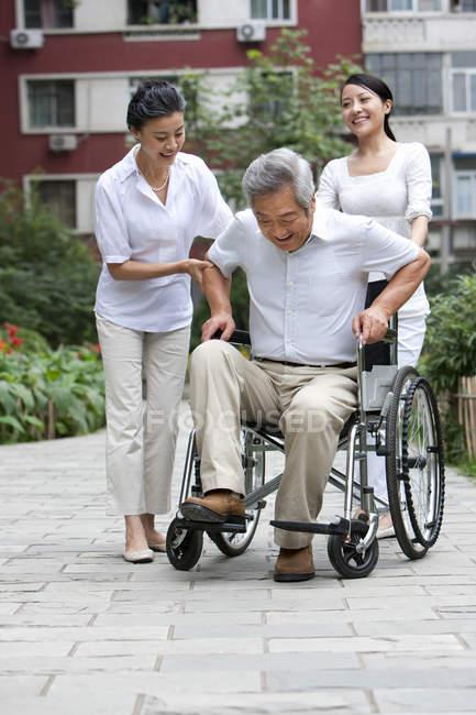Старший китаец встает с инвалидного кресла с женщинами на улице — стоковое фото