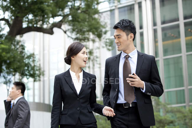 Chinese co-workers walking and chatting with smartphone in hand — Stock Photo