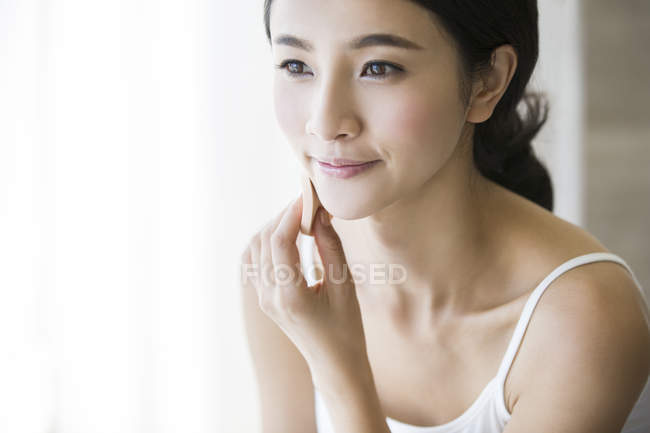 Young chinese woman applying face powder — Stock Photo