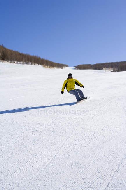 Молодой китайский человек, сноуборде на горнолыжном курорте — стоковое фото