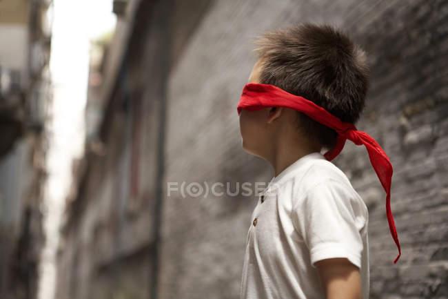 Menino com vendar jogo ocultar e procurar no beco — Fotografia de Stock
