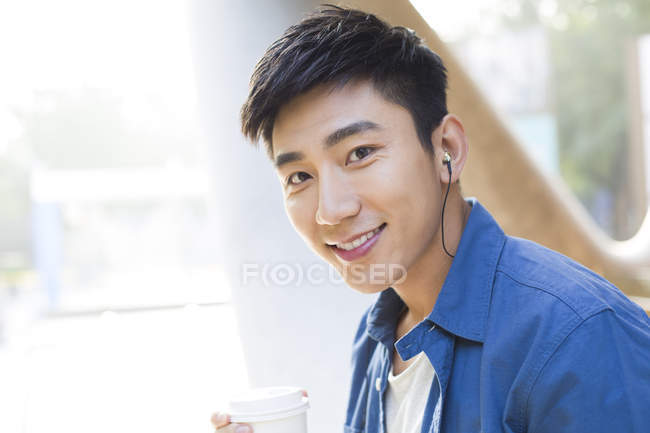 Chinese man holding coffee and listening music in earphones — Stock Photo