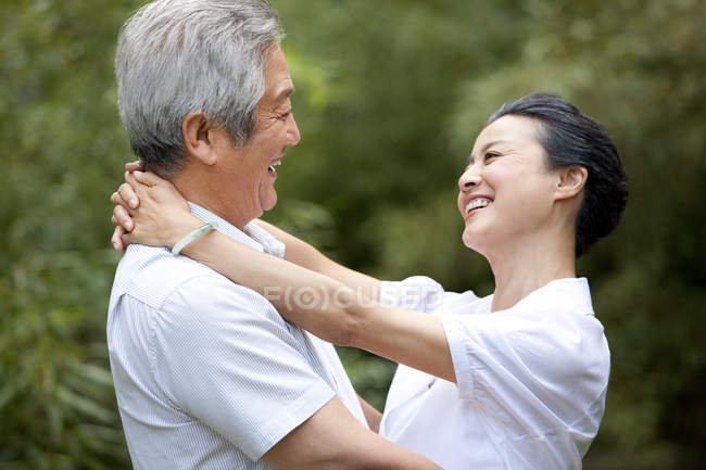 Chinese senior couple hugging each other outdoors — Stock Photo