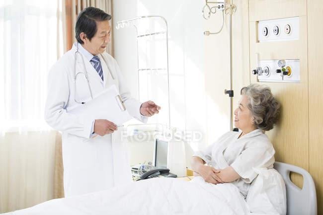 Китайский врач, говорить с пациентом в стационаре — стоковое фото