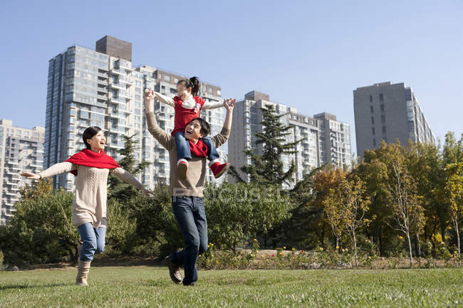 Chinese father carrying daughter on shoulders running with mother in park — Stock Photo