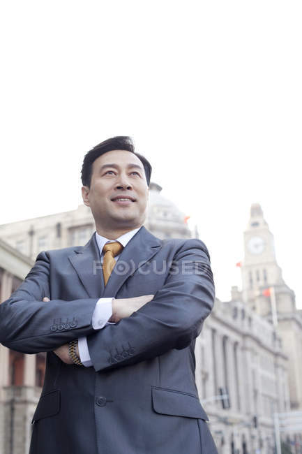 Portrait of Chinese businessman with arms crossed in city — Stock Photo