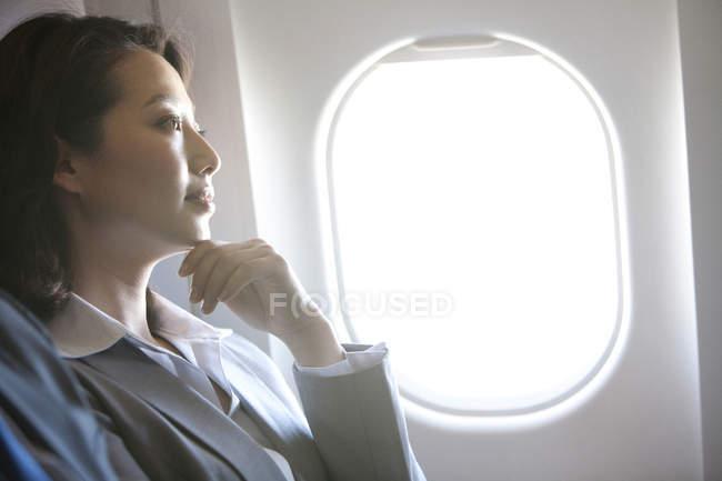 Chinese businesswoman thinking at plane — Stock Photo