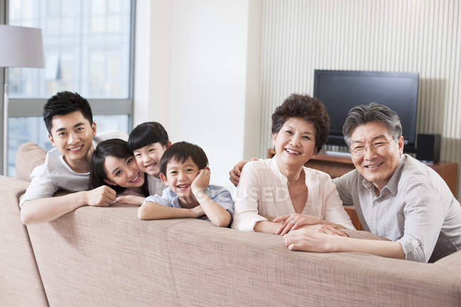 Chinese family of three generations sitting in a row on sofa — Stock Photo