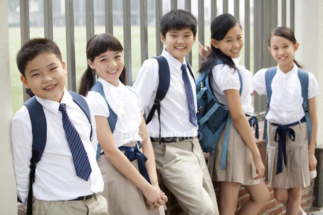 Estudantes chineses de uniforme escolar encostados à cerca — Fotografia de Stock