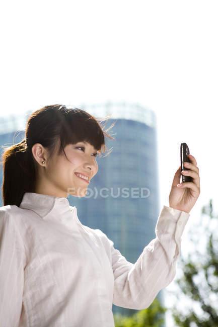 Empresária chinesa usando smartphone na frente do arranha-céu — Fotografia de Stock