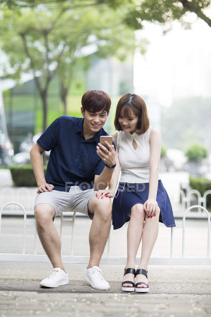 Young Chinese couple sharing earphones while listening to music — Stock Photo