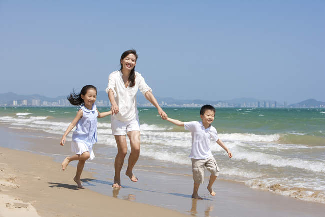 Китайський матері з дітьми працює на сонячному пляжі — стокове фото