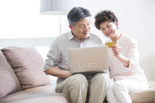 Senior Chinese couple shopping online with laptop — Stock Photo