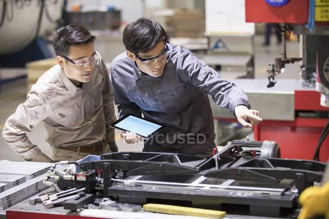 Confident Chinese engineers inspecting industrial equipment with digital tablet — Stock Photo