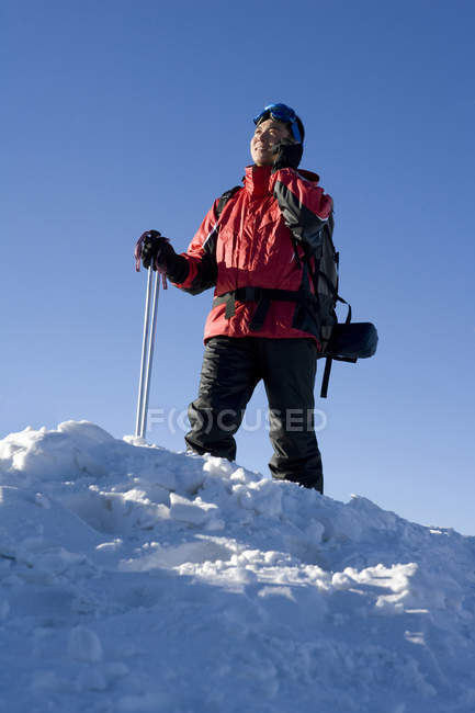 Chinese man with ski equipment talking on phone — Stock Photo