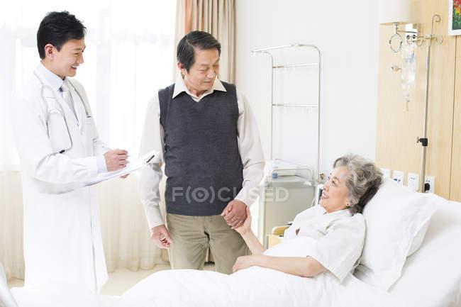 Médico chinês com casal sênior no hospital — Fotografia de Stock