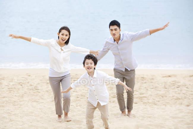 Chinesische Eltern mit Sohn läuft mit ausgestreckten Strand Sand — Stockfoto