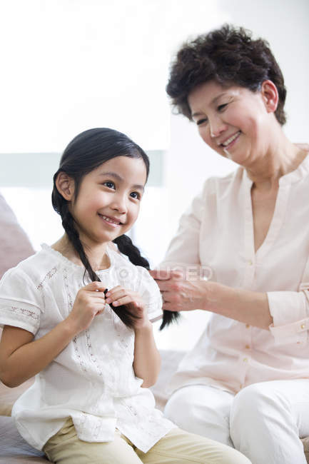 Chinese grandmother braiding granddaughter hair — Stock Photo