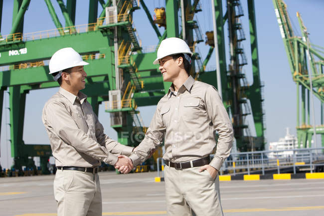 Male Chinese shipping industry workers shaking hands — Stock Photo