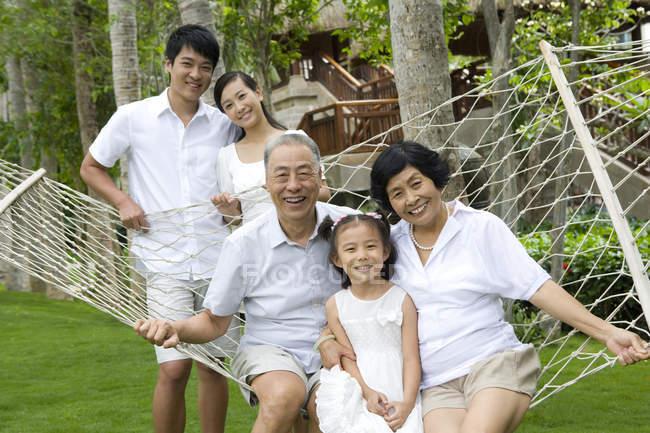 Família chinesa com rapariga descansando na rede — Fotografia de Stock