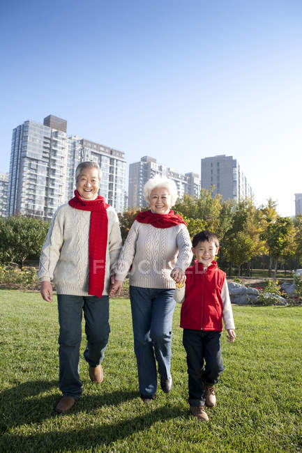 Chinese grandparents and grandson walking in park in autumn — Stock Photo