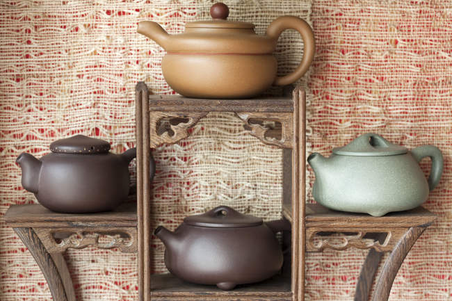 Traditional chinese teapots on wooden stand — Stock Photo