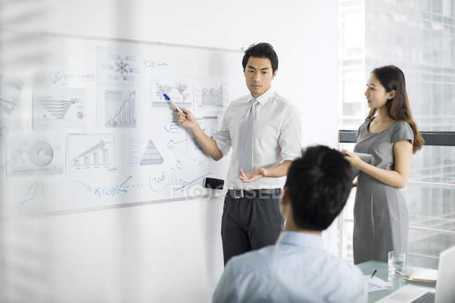 Homme d'affaires chinois faisant une présentation sur la réunion dans la salle de conseil — Photo de stock